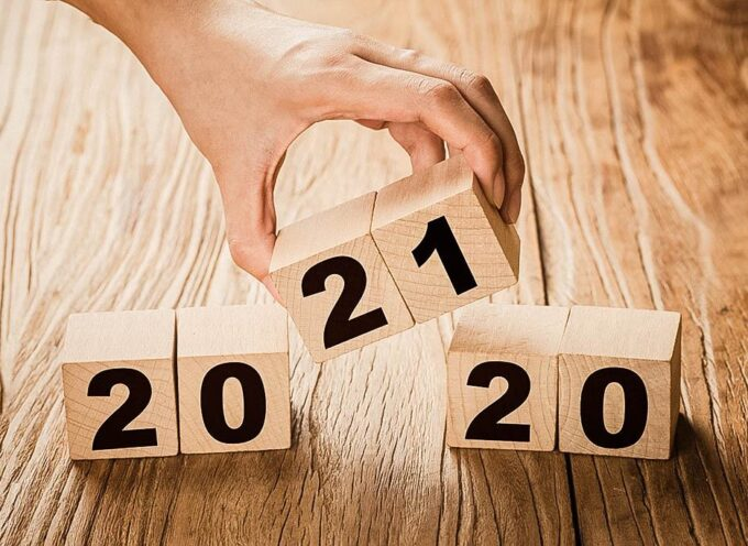 Hand flips a block changing 2020 to 2021. New year beginning. Holidays and Christmas.